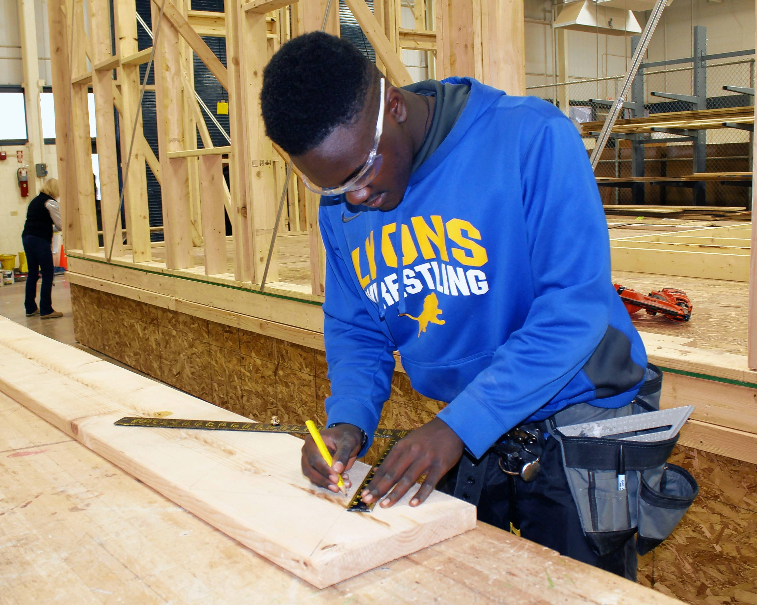 After calculating the number of risers and treads needed for a stairway project, Jerry Presley uses a carpenter's square to mark out the cuts on the stringers. Presley is a senior from Lyons Township High School in the construction trades program at Technology Center of DuPage.