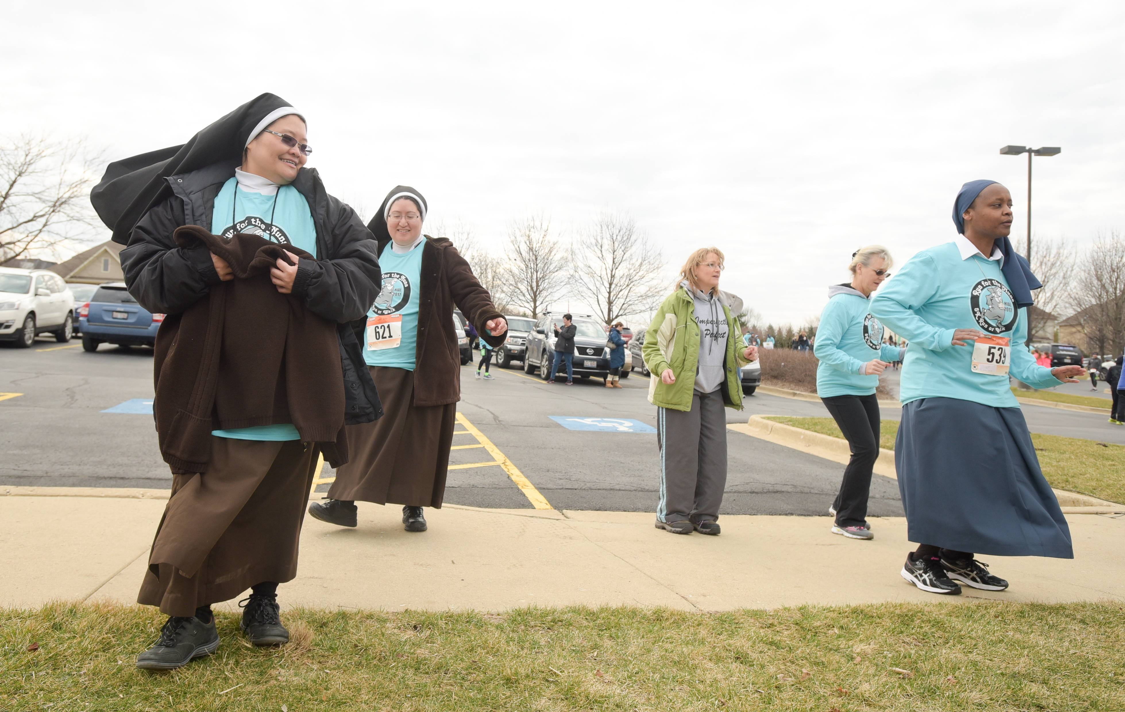 Sr. Rose Therese di Castro dances along with other runners before the start of the 3rd annual Run For The Nuns 5K Run/Walk, Sunday in South Elgin.