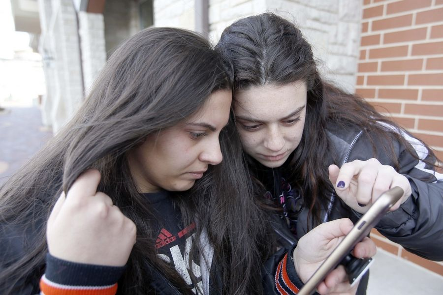 Antonia Galla, left, and Tatianna Lerario, both 17 and students at St. Charles East High School, look at pictures of Brittany S. Coffland and Tiffany S. Coffland, 16-year-old twins killed Friday in St. Charles. The friends were placing flowers at a memorial outside the building where the shootings occurred.