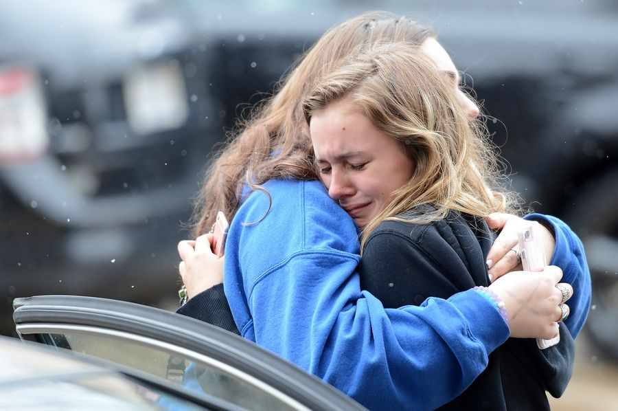 Sophia Licher, 17, right, gets a hug Monday from friend Emma Vitallo, 17, near the memorial for murdered St. Charles twins Tiffany and Brittany Coffland. The girls attended St. Charles East with the twins.