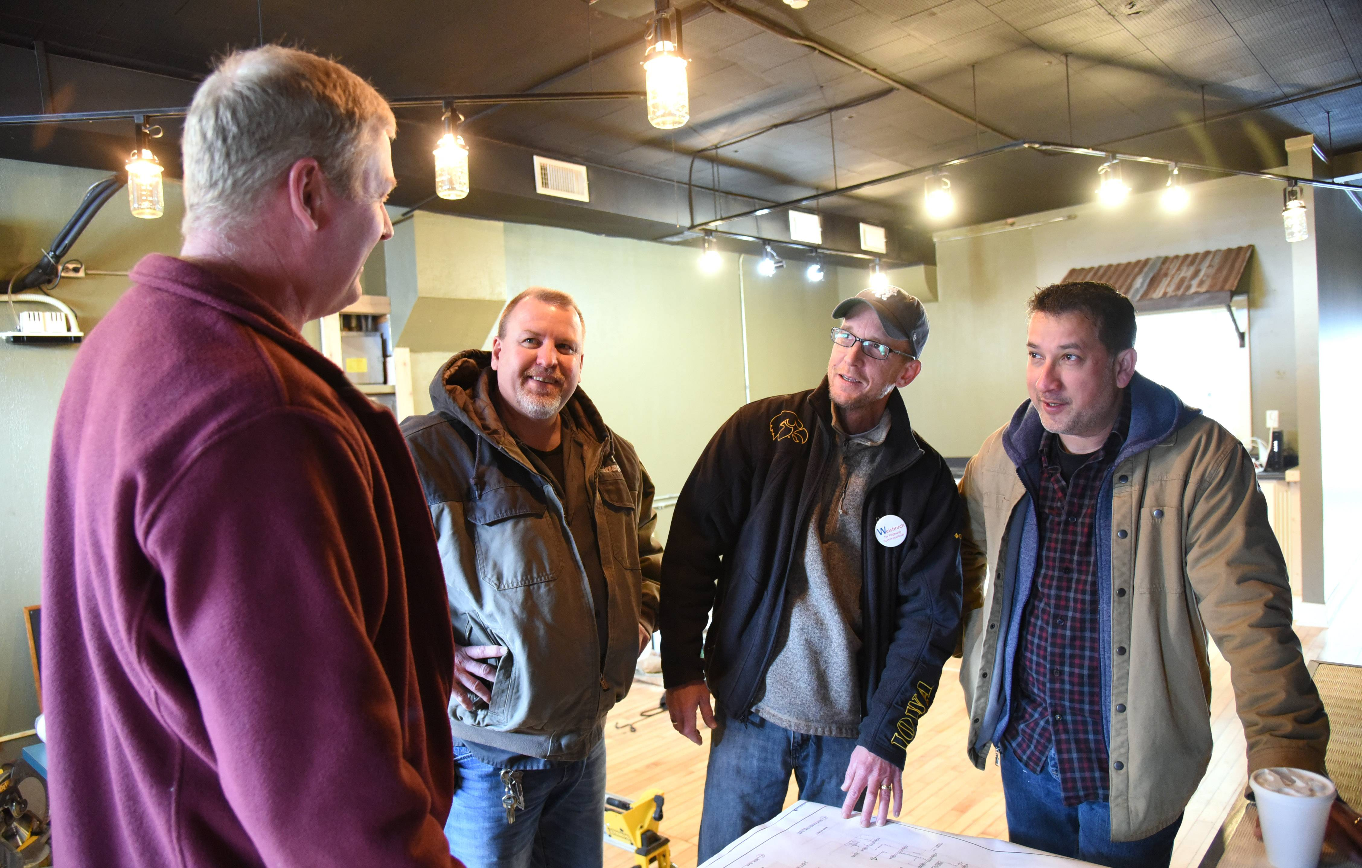 The Green Goat co-owners, from left, Jeff Middleton, Brian Middleton, Joe Kafka and Aaron Aggarwal, chat inside the restaurant space at 203 S. Main St. in downtown Wauconda. They plan to open the new eatery March 27.