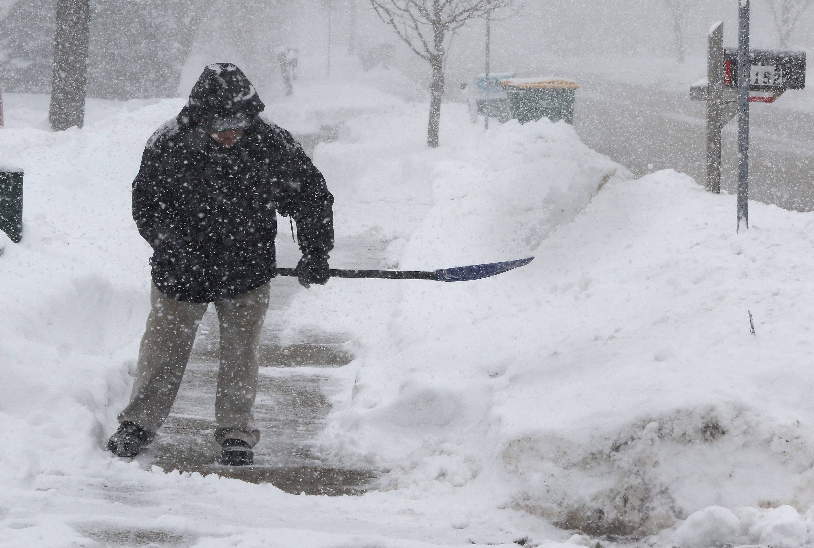 Gurnee resident Joe Belardi shovels out Tuesday. As much as 14 inches of snow fell in the area.