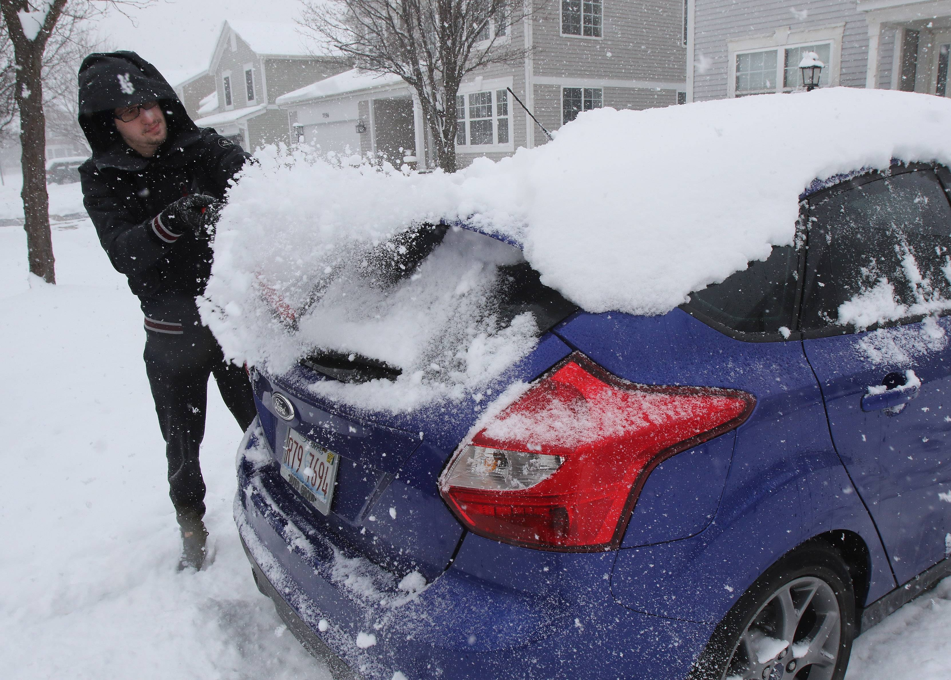 Gurnee resident Jason Volk clears the snow off his car outside his home on Tuesday.