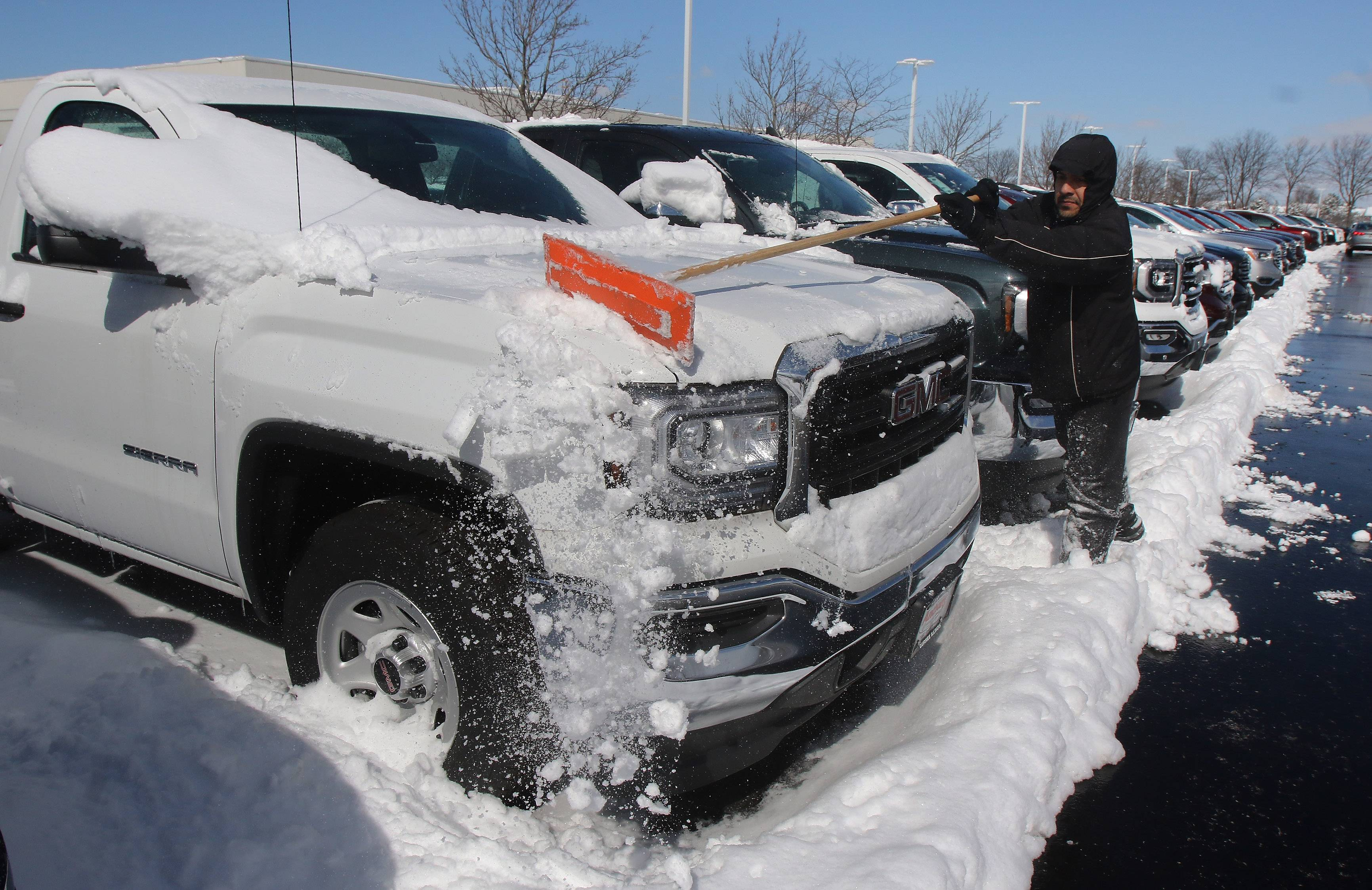 Salesman Carlos Brito cleans off the trucks at Anthony Buick in Gurnee on Tuesday. As much as 14 inches of snow fell in the area.