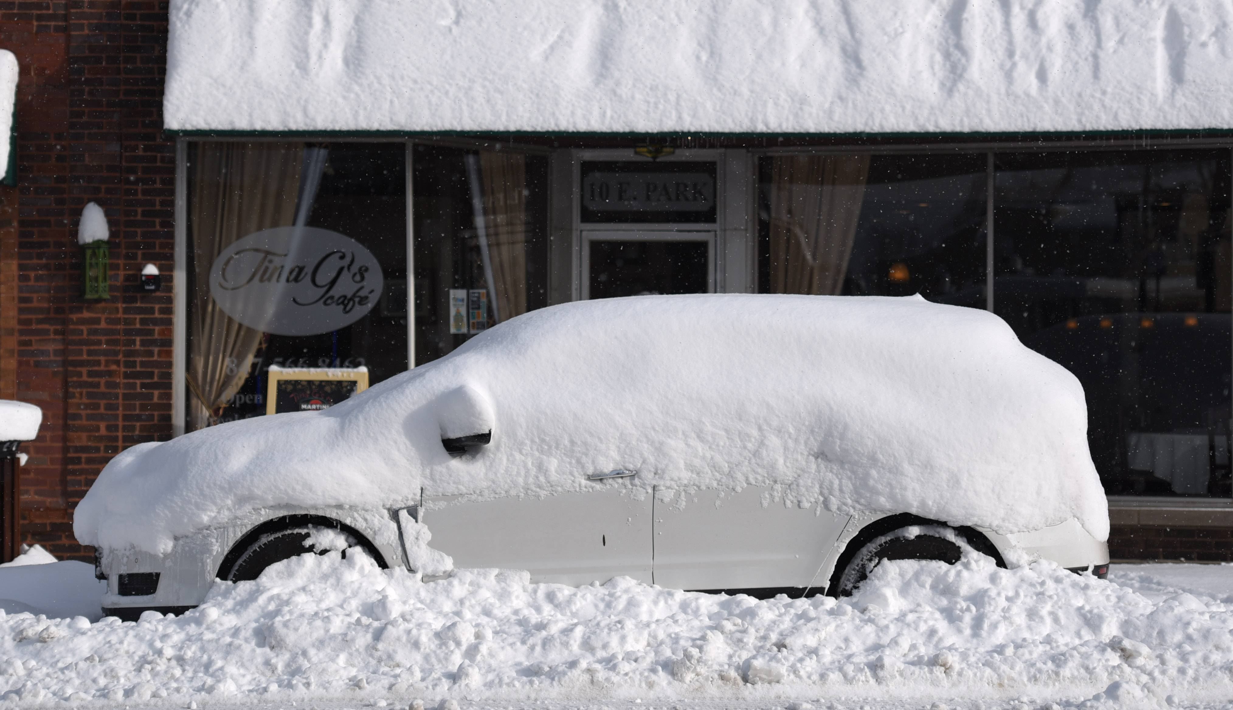 A car is buried in snow along East Park Street in downtown Mundelein Tuesday morning. Lake effect snow is kicking in and falling in parts of Lake County.