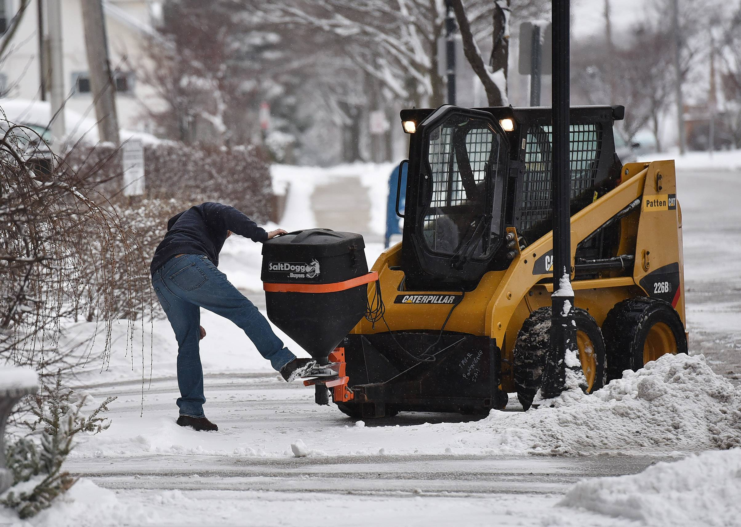 Richard Bazan gives a kick to free up some salt while salting the sidewalk in downtown Arlington Heights Monday morning.