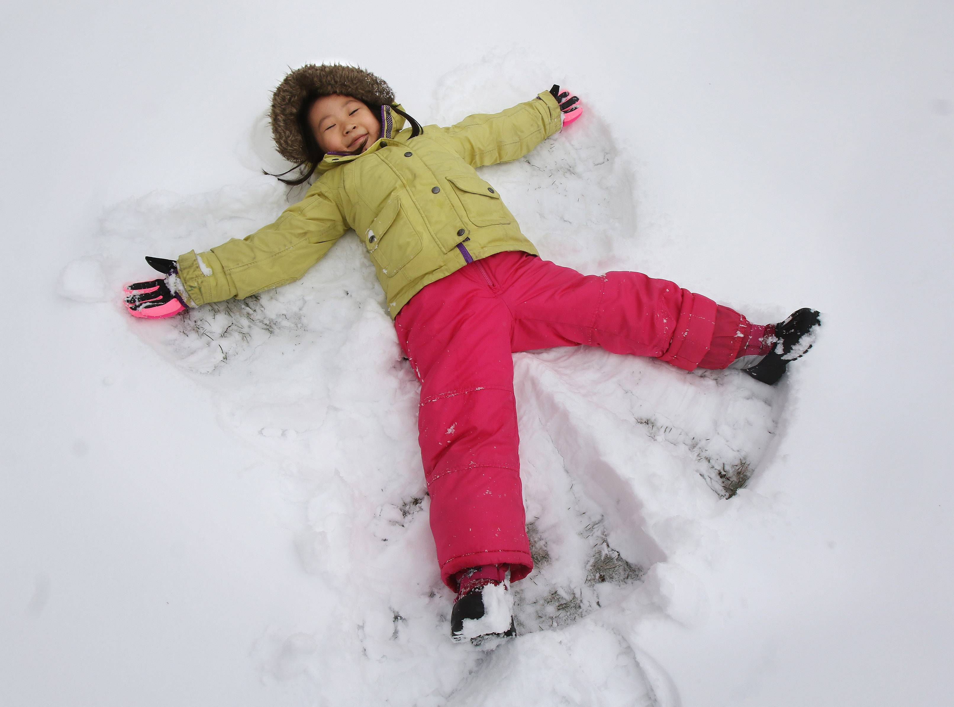 Five-year-old Claire Pyo makes a snow angel near her home in Vernon Hills on Monday after snow fell during the night before.