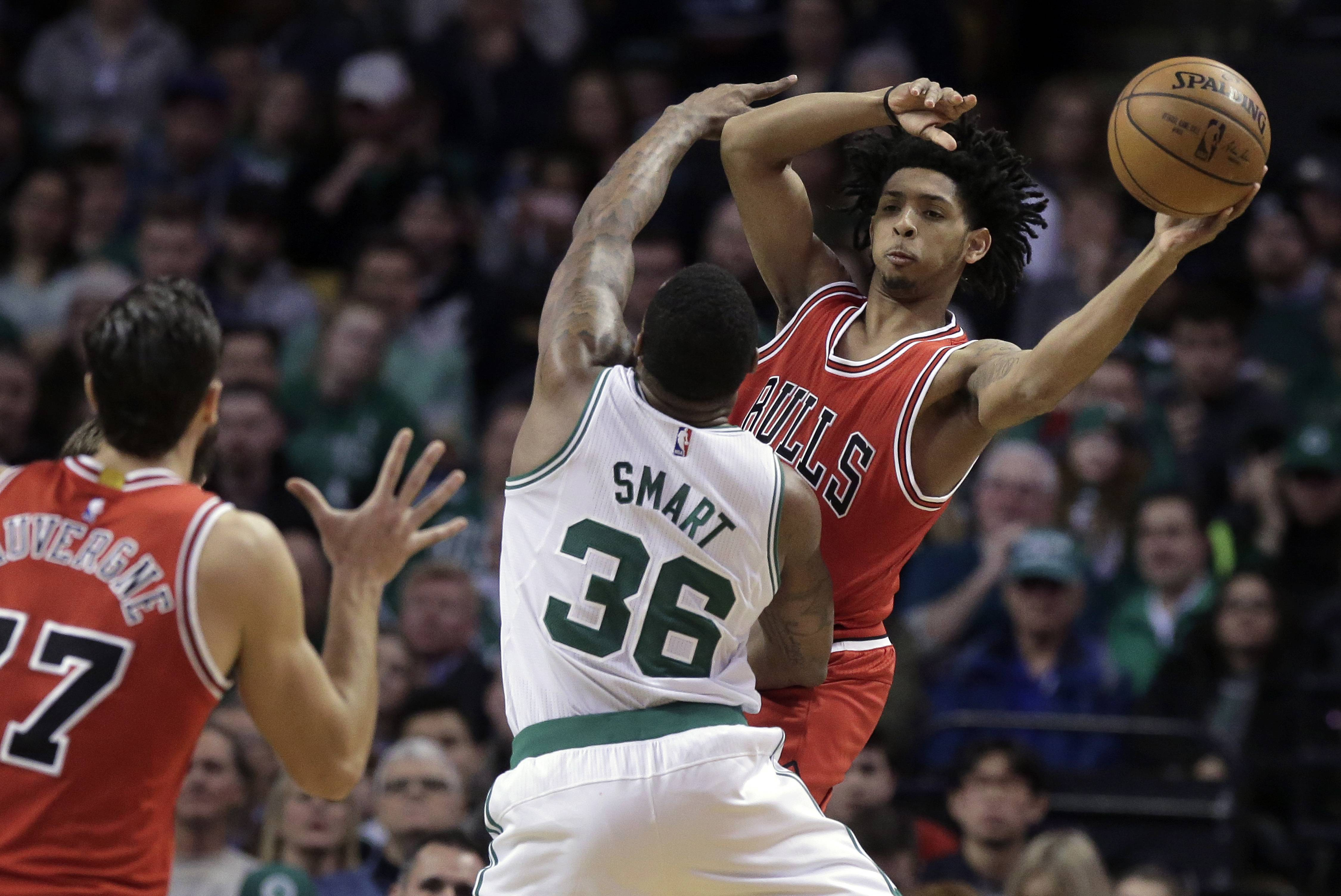 Chicago Bulls guard Cameron Payne, right, passes to Bulls center Joffrey Lauvergne, left, of France, as Boston Celtics guard Marcus Smart (36) tries to block him in the fourth quarter of an NBA basketball game, Sunday, March 12, 2017, in Boston.
