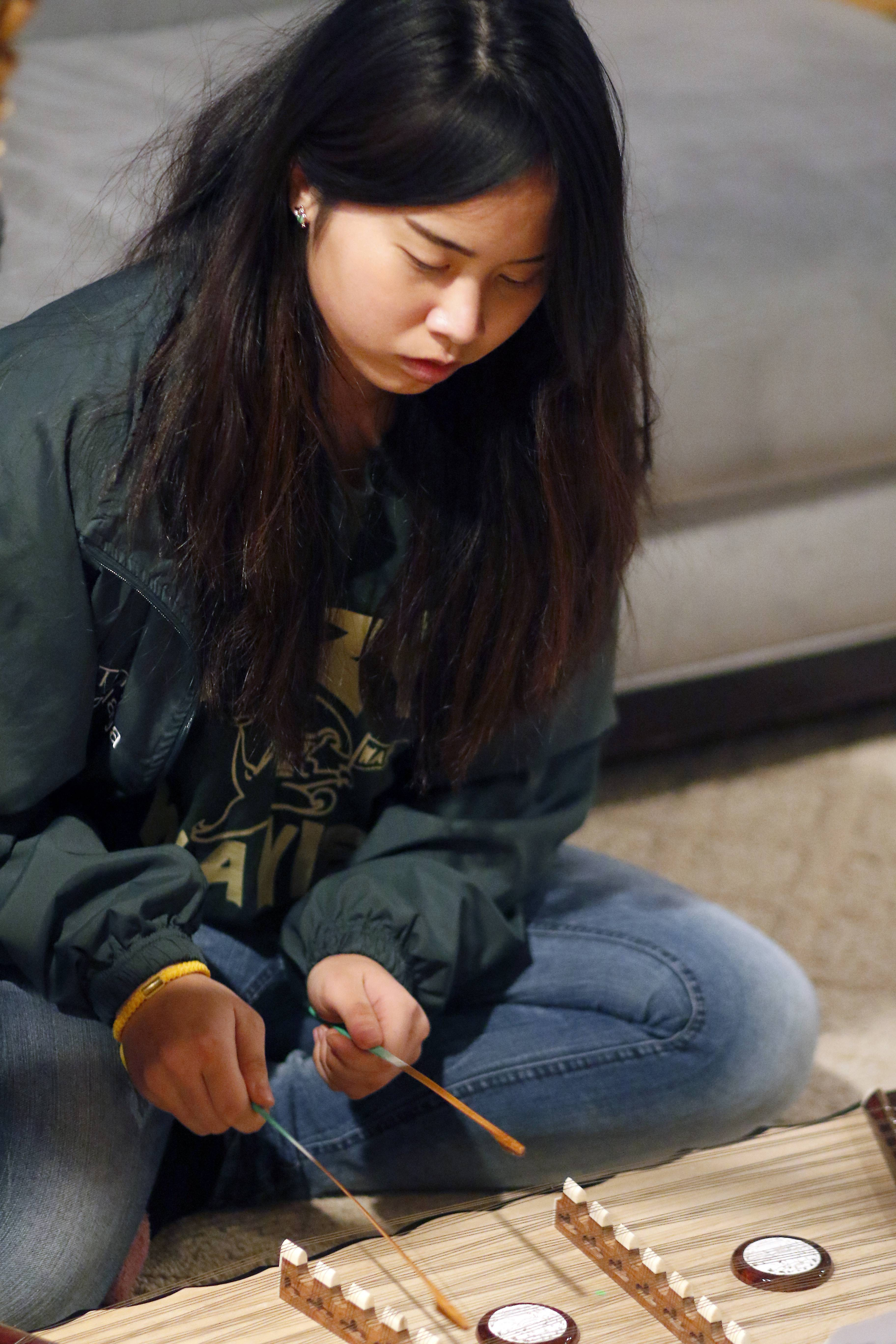 Tiffany Keokanlaya, 16, of South Elgin rehearses the khim, a traditional Lao instrument. The Lan Xang Traditional Lao Music & Dance Troupe aims to preserve Lao arts, music and culture.
