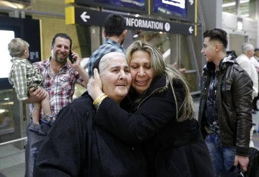 Nadia Hanan Madalo, center right, hugs her mother, Alyshooa Kannah, left, at the airport after arriving from Iraq Wednesday, March 15, 2017, in San Diego. Madalo and her family, refugees forced to flee their town of Batnaya, Iraq, after the Islamic State invaded and destroyed it several years ago, arrived in San Diego to be reunited with Madalo's siblings and mother. As they flew to the U.S. on Wednesday, a federal judge in Hawaii put a hold on President Trump's newest ban - the latest development in a fight between the administration and the courts that has injected more uncertainty into the lives of refugees.