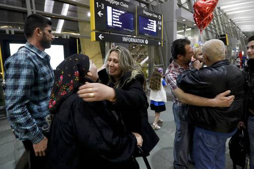 Nadia Hanan Madalo, center right, hugs her mother, Alyshooa Kannah, center left, at the airport after arriving from Iraq Wednesday, March 15, 2017, in San Diego. Madalo and her family, refugees forced to flee their town of Batnaya, Iraq, after the Islamic State invaded and destroyed it several years ago, arrived in San Diego to be reunited with Madalo's siblings and mother. As they flew to the U.S. on Wednesday, a federal judge in Hawaii put a hold on President Trump's newest ban - the latest development in a fight between the administration and the courts that has injected more uncertainty into the lives of refugees.