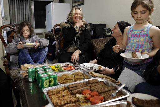 Nadia Hanan Madalo, center, talks with her mother, Alyshooa Kannah, second from right, and other family members as she sits down for a meal in her brother's apartment Thursday, March 16, 2017, in El Cajon, Calif, after arriving to the United States. Madalo and her family, refugees forced to flee their town of Batnaya, Iraq, after the Islamic State invaded and destroyed it several years ago, arrived in San Diego to be reunited with Madalo's siblings and mother. As they flew to the U.S. on Wednesday, a federal judge in Hawaii put a hold on President Trump's newest ban - the latest development in a fight between the administration and the courts that has injected more uncertainty into the lives of refugees.
