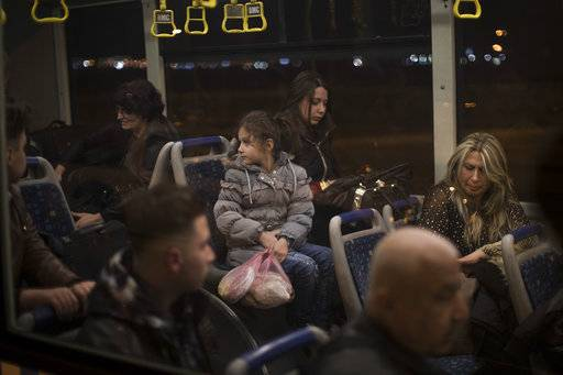 Noor, 8, center, sits with her sister Maryam, 18, and their mother Nadia Hanan Madalo, 46, right, as they wait in an airport bus in Irbil, Iraq, Wednesday, March 15, 2017. An Iraqi family has landed in the United States as a federal court blocked a travel ban that would have kept others like them out of the country for 120 days. Madalo and her family arrived in San Diego to be reunited with Madalo's siblings and mother, who arrived as refugees in recent years.