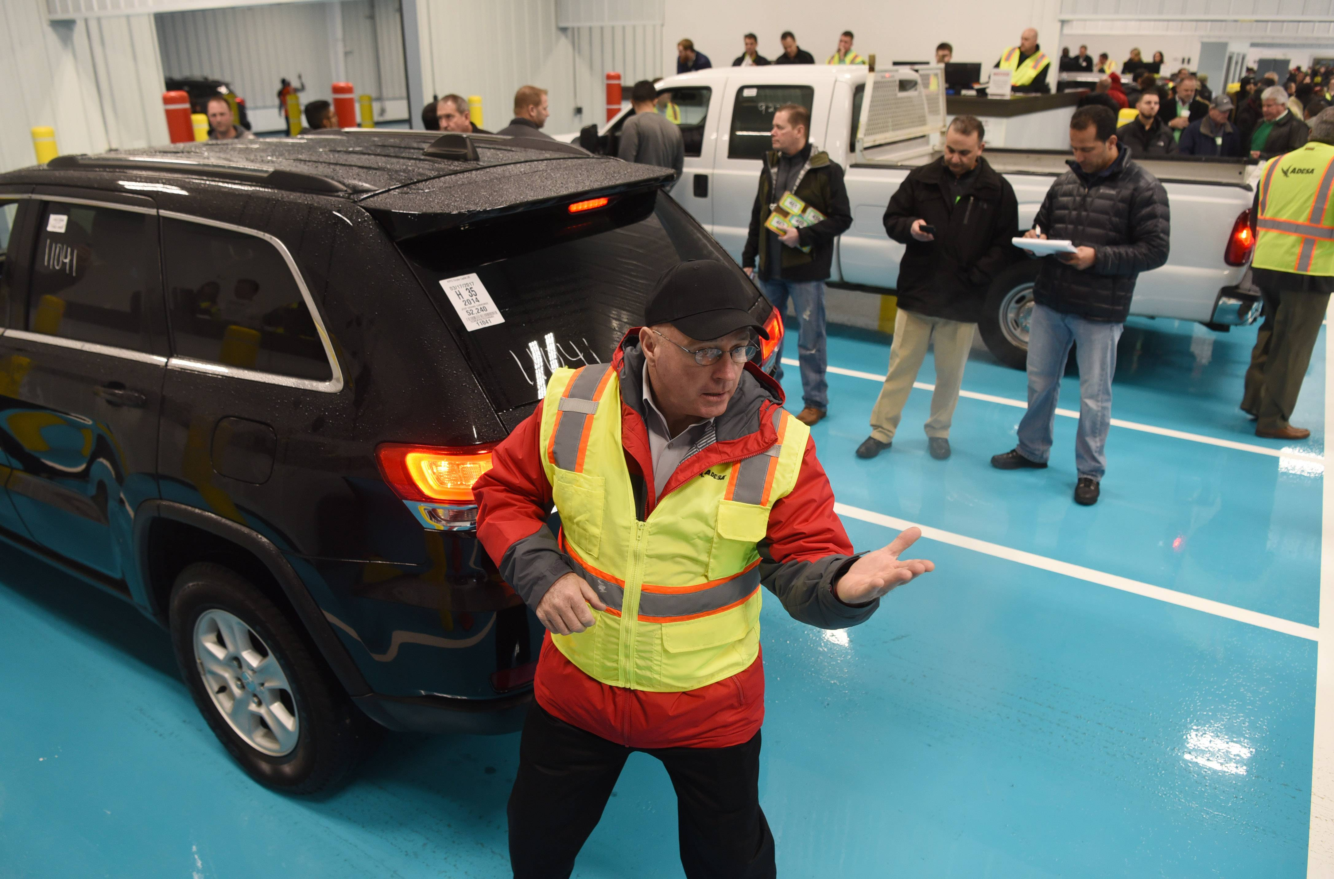 Ringman Mike Welch points toward bidders as cars are sold Friday during the grand opening of Adesa Chicago's vehicle auction facility in Hoffman Estates.