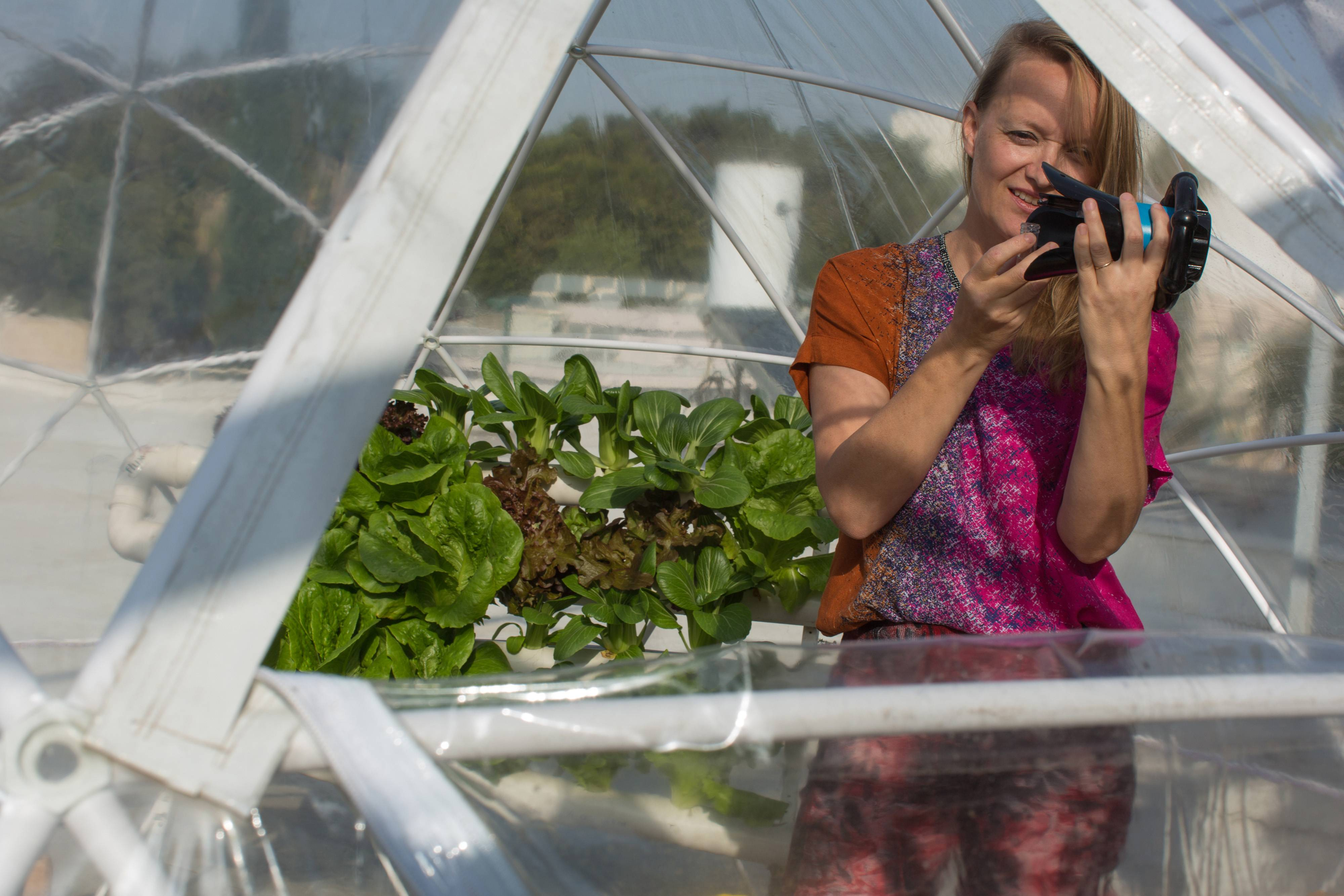 "Karin Kloosterman, co-founder of Flux IoT, prepares her tiny robot ""Eddy,"" which can detect nutrient deficiency in plants, in a pop up greenhouse during its development to help produce food from water in the Jaffa district of Tel Aviv, Israel, on Feb. 26, 2017. Bloomberg photo by Rina Castelnuovo."