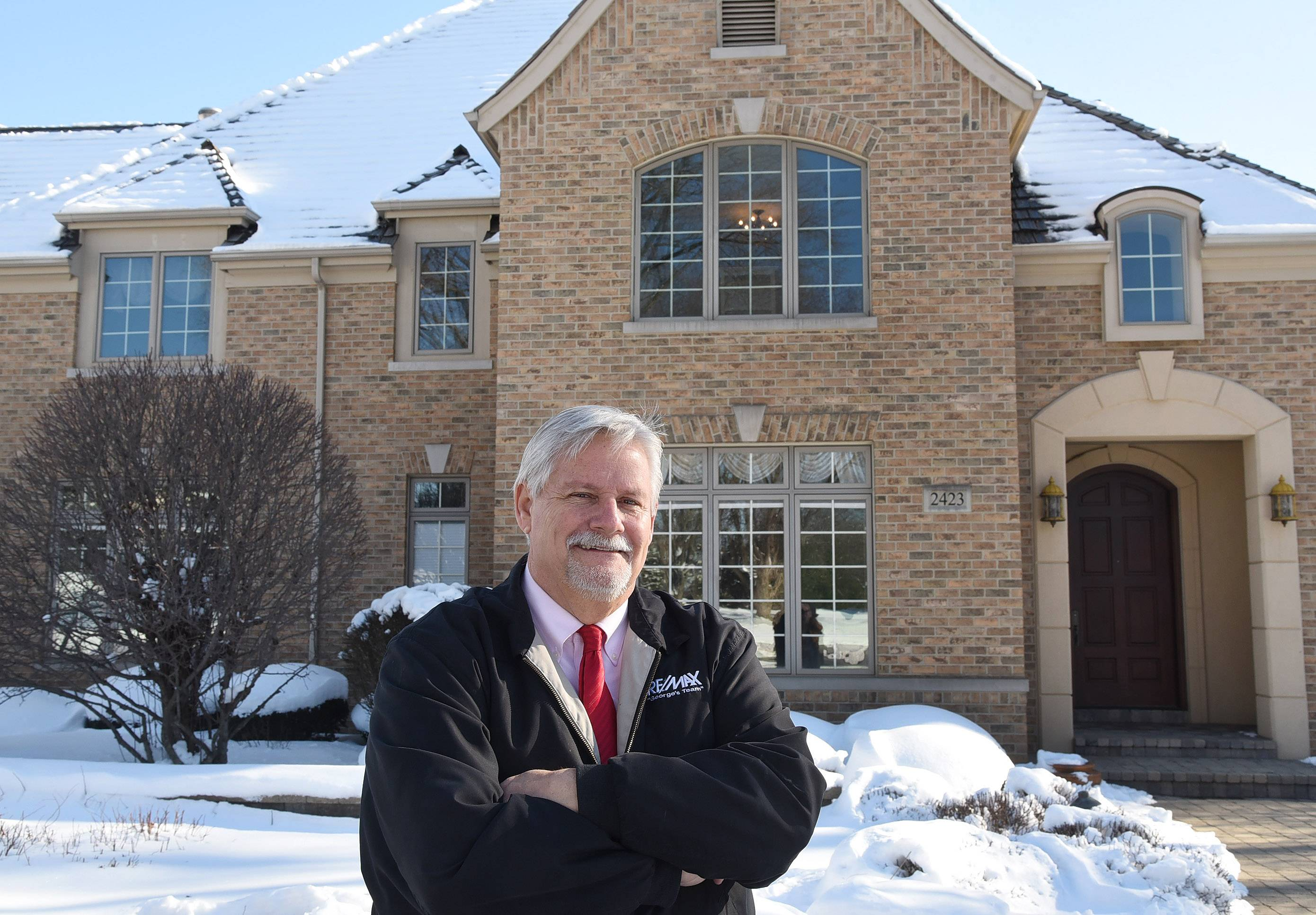George Seaverns, a RE/MAX agent from Buffalo Grove, in front of one of his listings on Cumberland Circle in Long Grove.