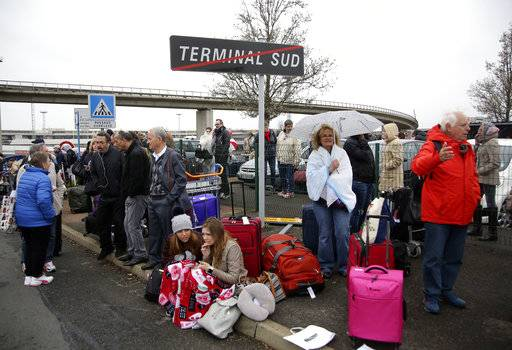 Travelers wait outside the Orly airport , south of Paris, Saturday, March, 18, 2017. A man was shot dead after wrestling a soldier to the ground at Paris' Orly Airport and trying to take her rifle, officials said. No one else in the busy terminal was hurt, but thousands of travelers were evacuated and flights were diverted to the city's other airport.