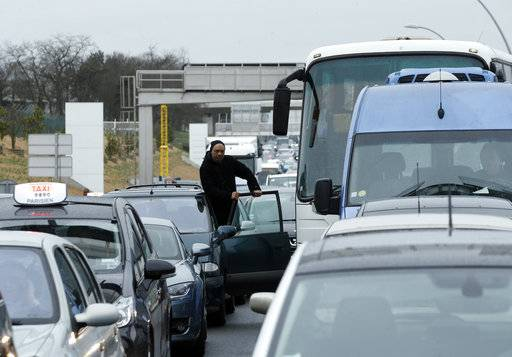 A man watches the traffic on the highway leading to the Orly airport, south of Paris, Saturday, March, 18, 2017. A man was shot to death Saturday after trying to seize the weapon of a soldier guarding Paris' Orly Airport, prompting a partial evacuation of the terminal, police said.