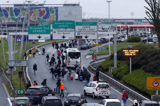 Travellers walk on the highway to the Orly airport, south of Paris, Saturday, March, 18, 2017. A man was shot to death Saturday after trying to seize the weapon of a soldier guarding Paris' Orly Airport, prompting a partial evacuation of the terminal, police said.