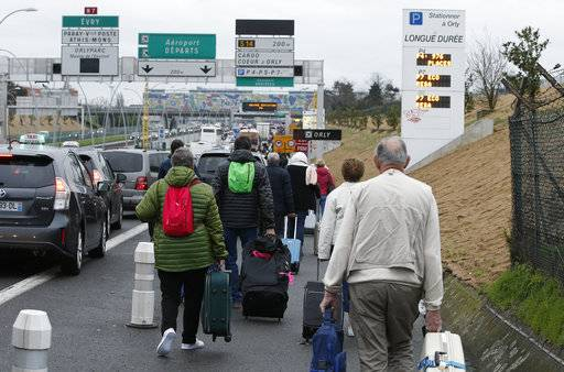 Travellers walk on the highway to the Orly airport, south of Paris, Saturday, March, 18, 2017. French police say a man was shot to death after trying to seize the weapon of a soldier guarding Paris' Orly Airport.