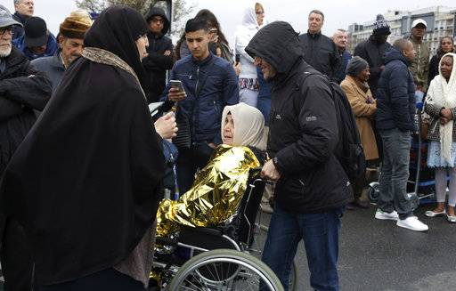 A woman in a wheelchair is helped to evacuate the Orly airport, south of Paris, Saturday, March, 18, 2017. A man was shot to death Saturday after trying to seize the weapon of a soldier guarding Paris' Orly Airport, prompting a partial evacuation of the terminal, police said. Authorities warned visitors to avoid the area while an ongoing police operation was underway.
