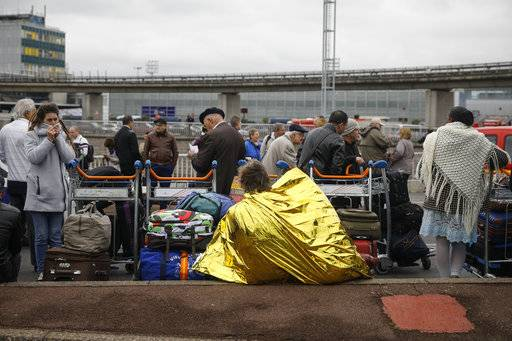 Travelers wait outside Orly airport, south of Paris, Saturday, March, 18, 2017. Soldiers at Paris' busy Orly Aiport shot and killed a man who wrestled one of their colleagues to the ground and tried to steal her rifle Saturday, officials said.