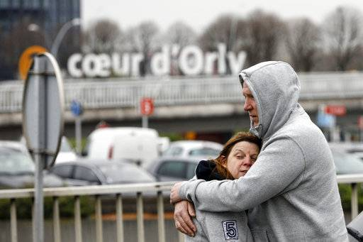 Travelers hug outside Orly airport, south of Paris, Saturday, March, 18, 2017. A man was shot to death Saturday after trying to seize the weapon of a soldier guarding Paris' Orly Airport, prompting a partial evacuation of the terminal, police said.