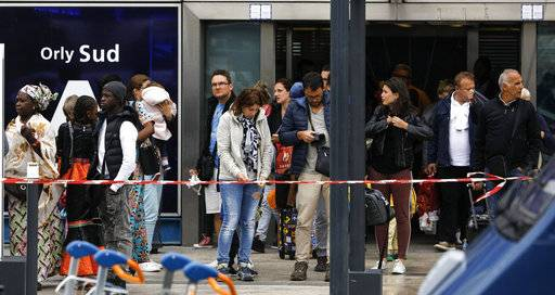 Travelers evacuate Orly airport, south of Paris, Saturday, March, 18, 2017. Soldiers at Paris' busy Orly Aiport shot and killed a man who wrestled one of their colleagues to the ground and tried to steal her rifle Saturday, officials said.