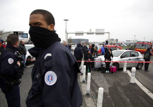 A French police officer guards travelers waiting outside the Orly airport , south of Paris, Saturday, March, 18, 2017. A man was shot dead after wrestling a soldier to the ground at Paris' Orly Airport and trying to take her rifle, officials said. No one else in the busy terminal was hurt, but thousands of travelers were evacuated and flights were diverted to the city's other airport.