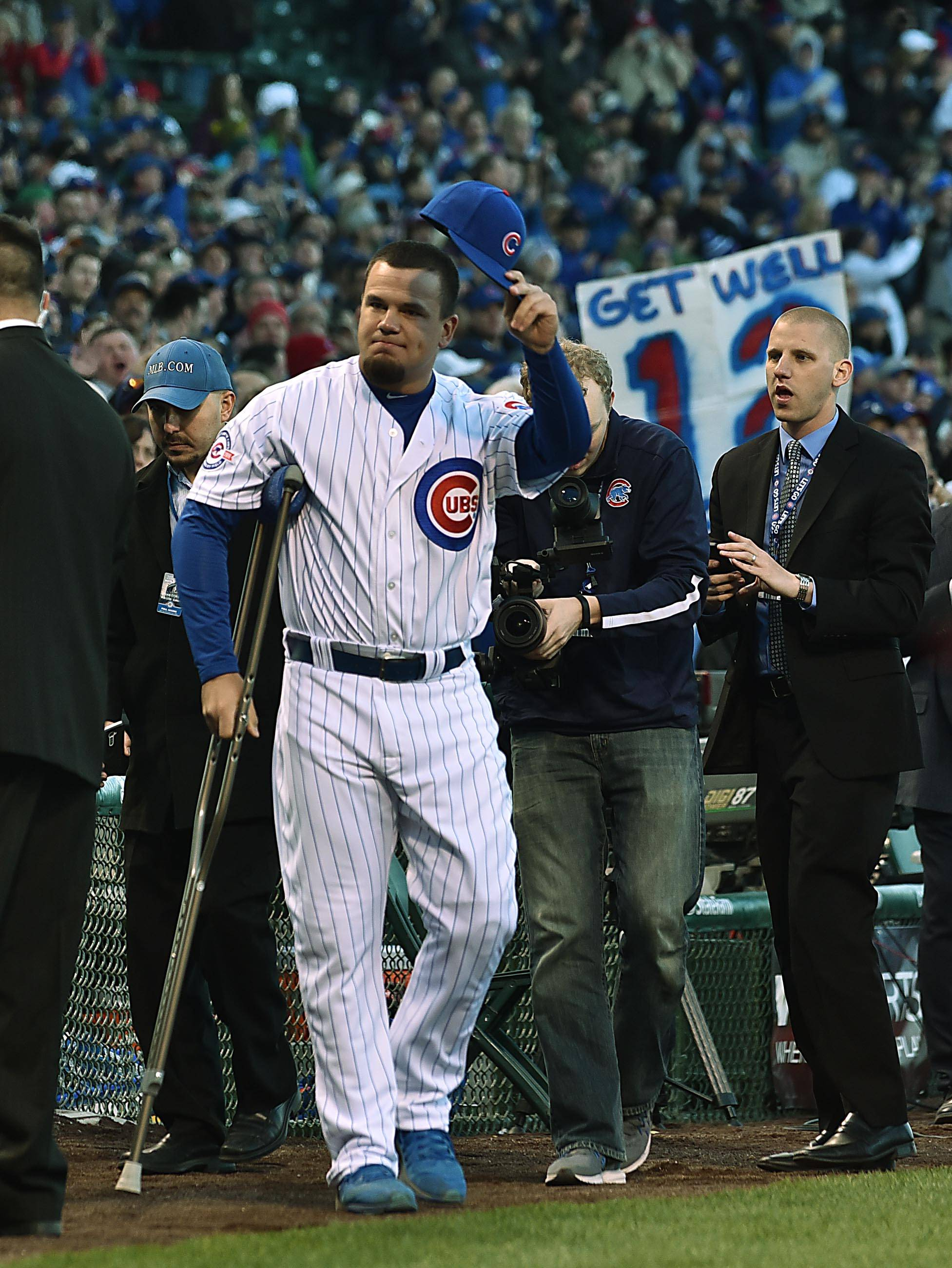 Chicago Cubs left fielder Kyle Schwarber tips his hat to the crowd as his comes on to the field using crutches on opening day at Wrigley Field in Chicago. Schwarber missed the entire regular season, but returned to help the Cubs win the World Series.