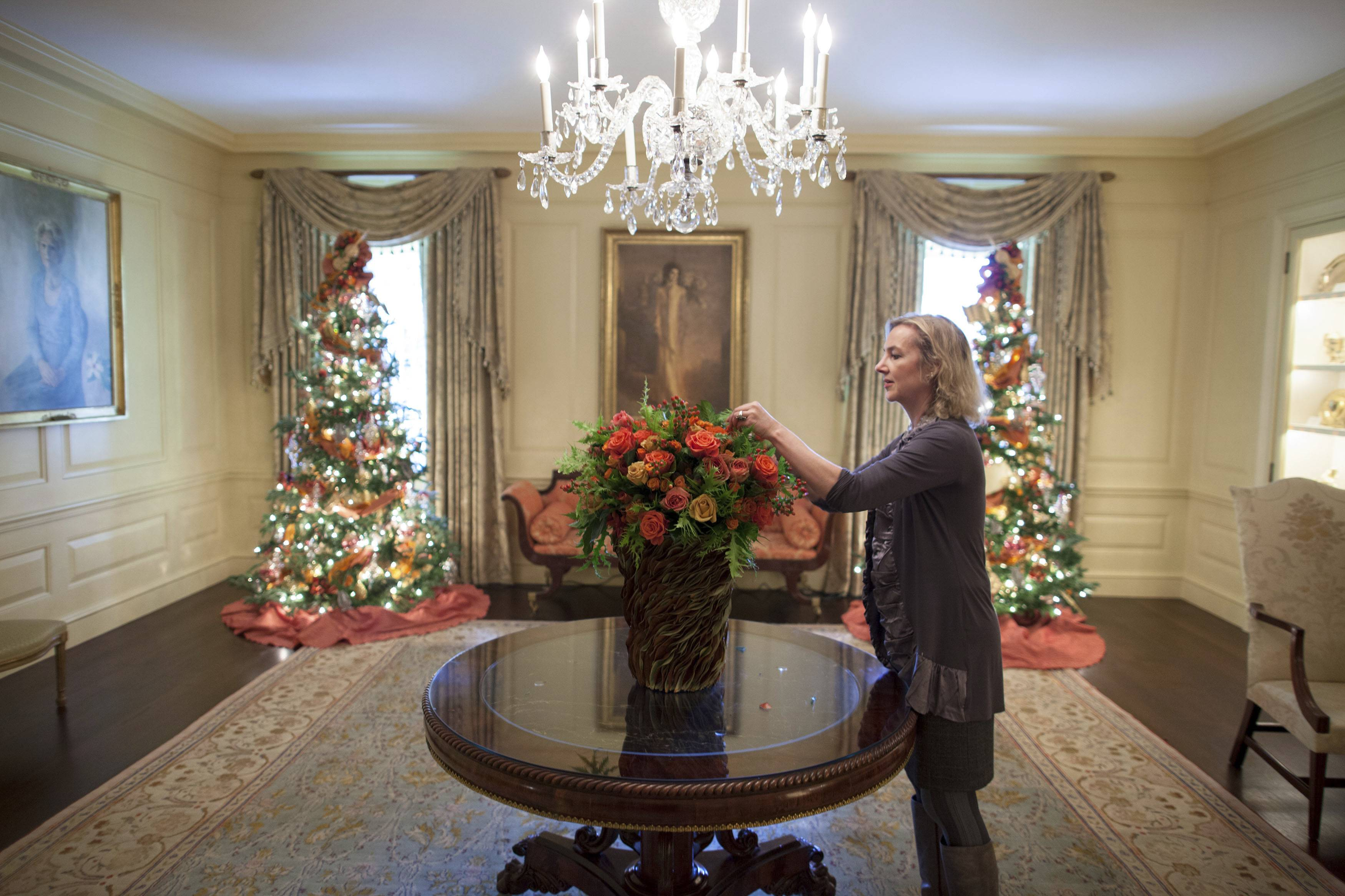 Laura Dowling completes a holiday arrangement of peach and coral roses in a magnolia leaf vase in the Vermeil Room, before the launch of the White House Christmas season, with the Aaron Shikler portrait of first lady Jacqueline Kennedy in the background.