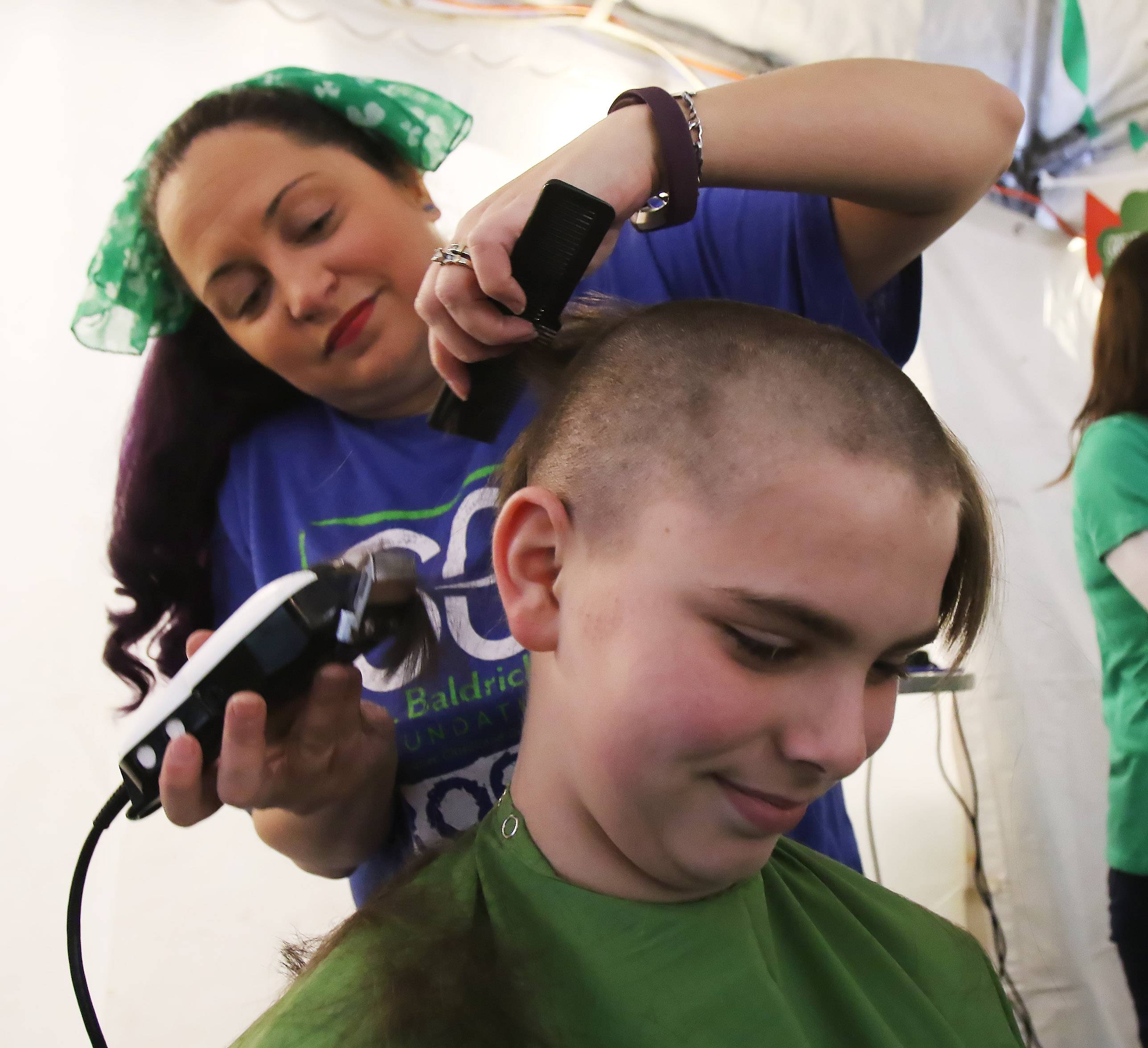 Ryan Siegel, 13, of Lake Zurich gets his head shaved by Shelly Healy of Volo during the Wauconda Community Shave event Sunday to help find a cure for pediatric cancer. More than 75 people were expected to have their heads shaved to help the St. Baldrick's Foundation.