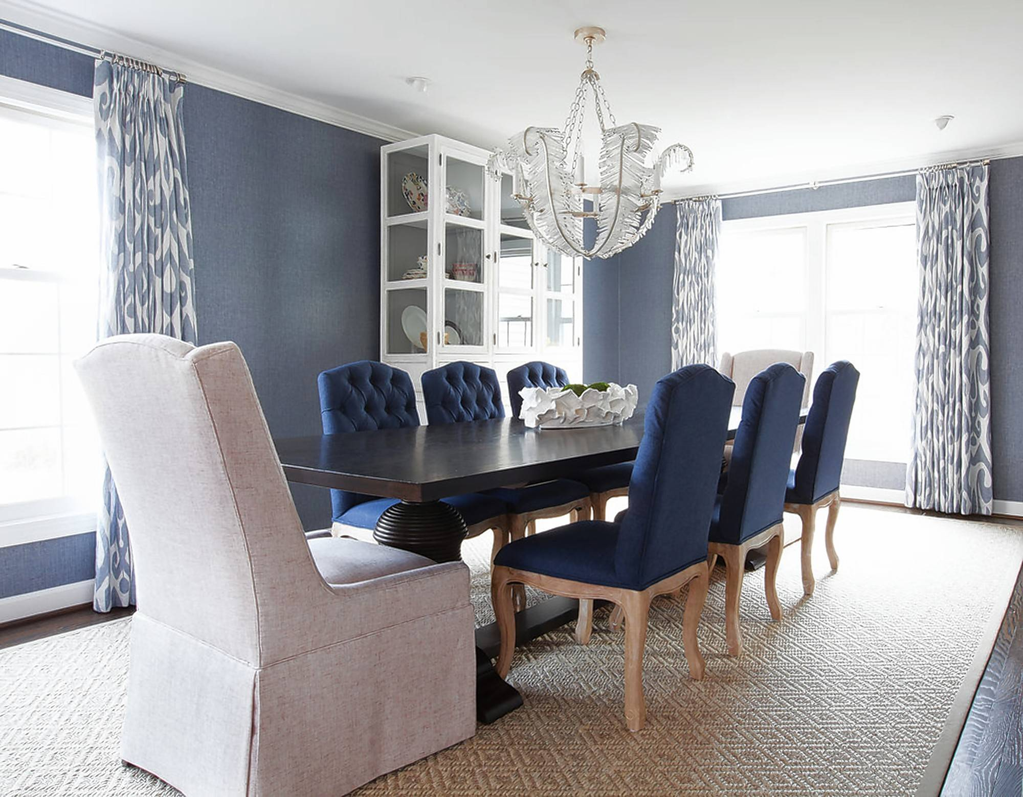 A dining room in Bethesda, Maryland, designed by Erica Burns uses contrasting host chairs at the ends of the table to avoid a matchy-matchy look.