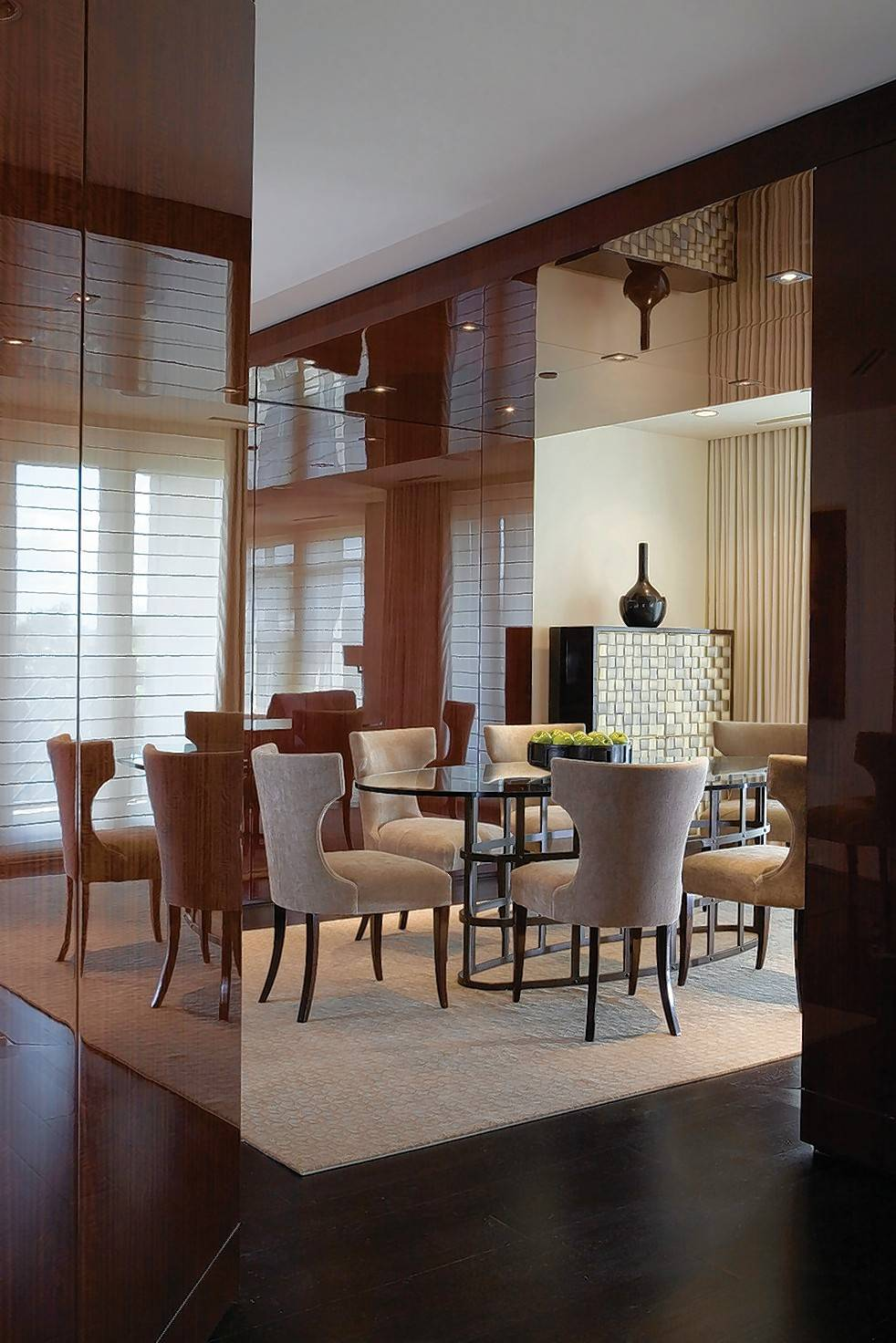 A Washington, D.C., condo dining room designed by Thomas Pheasant features dark stained mahogany panels on walls and ceilings that contrast with bronze and steel finishes on the furnishings.