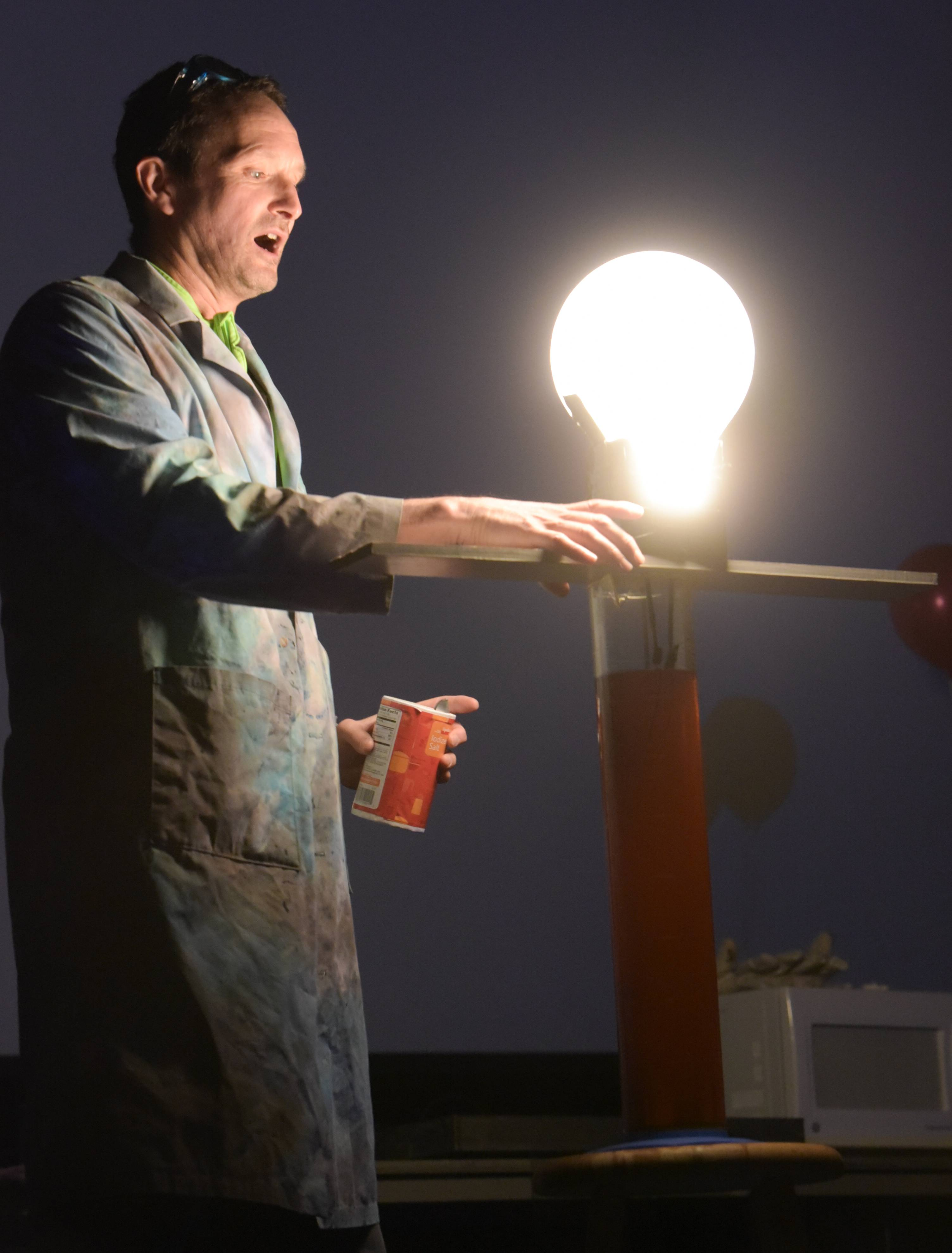 Bill Grosser, teacher at Oak Park and River Forest High School, uses electrolytes, salt and water to conduct electricity to light up a light bulb during the 30th annual Wonders of Science at Fermilab in Batavia.