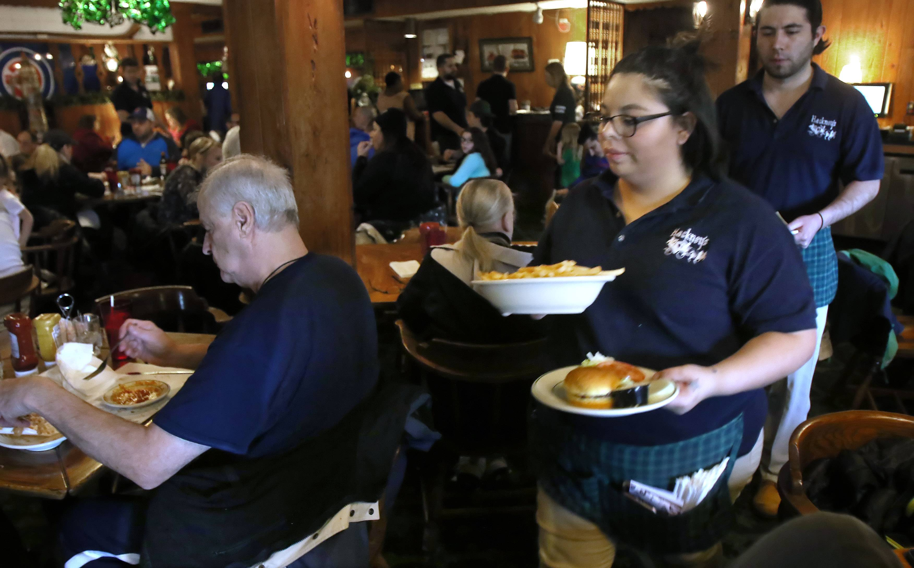 Waitress Laura Colorado delivers food to a table Sunday, the last day of business for Hackney's in Lake Zurich. After a 48-year run, the restaurant's owners decided to close it for good Sunday.