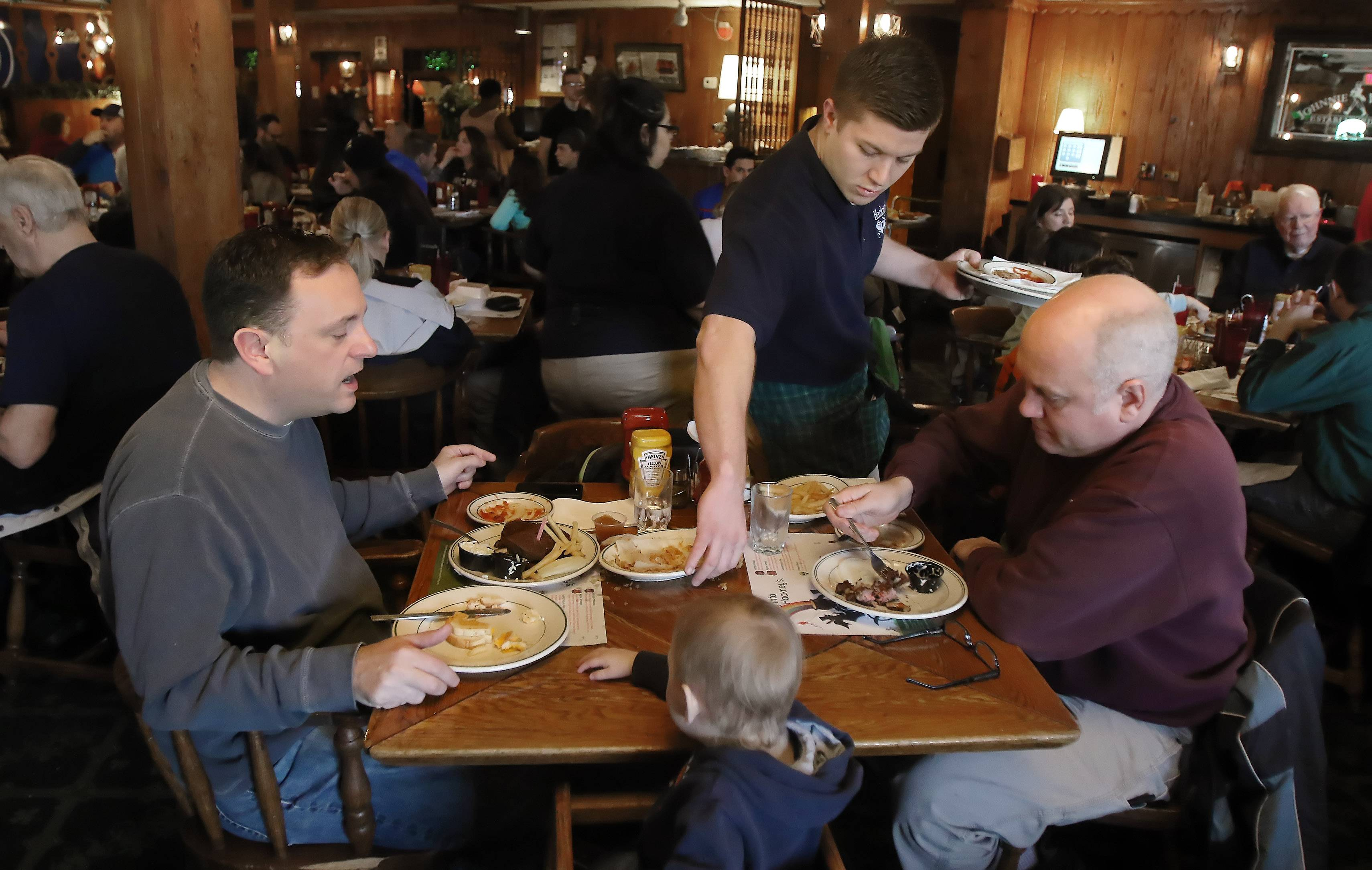 Waiter Patrick Miller waits on John Molitor of Port Barrington, left, his son, Johnny, and Laris Vigants of Fox River Grove on the last day of business for Hackney's in Lake Zurich on Sunday. The restaurant has been open for 48 years.