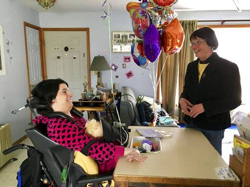 In this March 11, 2017 photo, Stephanie Bushey, right, uses sign language and eye movements to communicate with her daughter, Katie, at their home in West Chazy, N.Y. Katie, who lost her vocal and motor skills at birth, relies on assistance from home health aides during the day while her mother is at work. Advocates for the disabled, elderly and chronically ill in New York are concerned the state's move to a $15 minimum wage could deepen a shortage of home health aides. (AP Photo/Anna Gronewold)