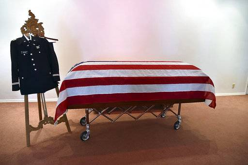 "In this March 15, 2017 photo, the remains of Maax Curtis Hammer Jr., sit in Carbondale, Ill., who was a Flying Tiger from Cairo, Ill. They were returned home via dignified transport from Hawaii, where he had been buried for 67 years in a grave marked ""Unknown."" A U.S. Army uniform, dedicated to Hammer, but without his medals, is positioned near the head of his casket at a funeral home. Hammer was part of the Flying Tigers, a group of volunteer pilots who helped the British and Chinese defend what was Burma and China from the Japanese. (Richard Sitler/The Southern Illinoisan via AP)"