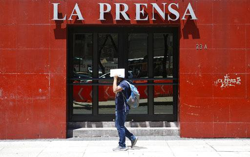 A man shields his face from the sun as he walks past the offices of tabloid newspaper La Prensa on Paseo de la Reforma in Mexico City, Monday, March 20, 2017. The mystery of Tom Brady's missing Super Bowl jersey led police all the way to Mexico, and authorities were investigating a former tabloid newspaper executive's possible role in the case.