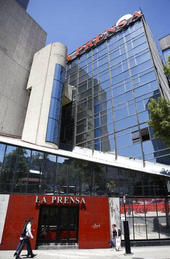 People walk past the offices of tabloid newspaper La Prensa on Paseo de la Reforma in Mexico City, Monday, March 20, 2017. The mystery of Tom Brady's missing Super Bowl jersey led police all the way to Mexico, and authorities were investigating a former tabloid newspaper executive's possible role in the case.