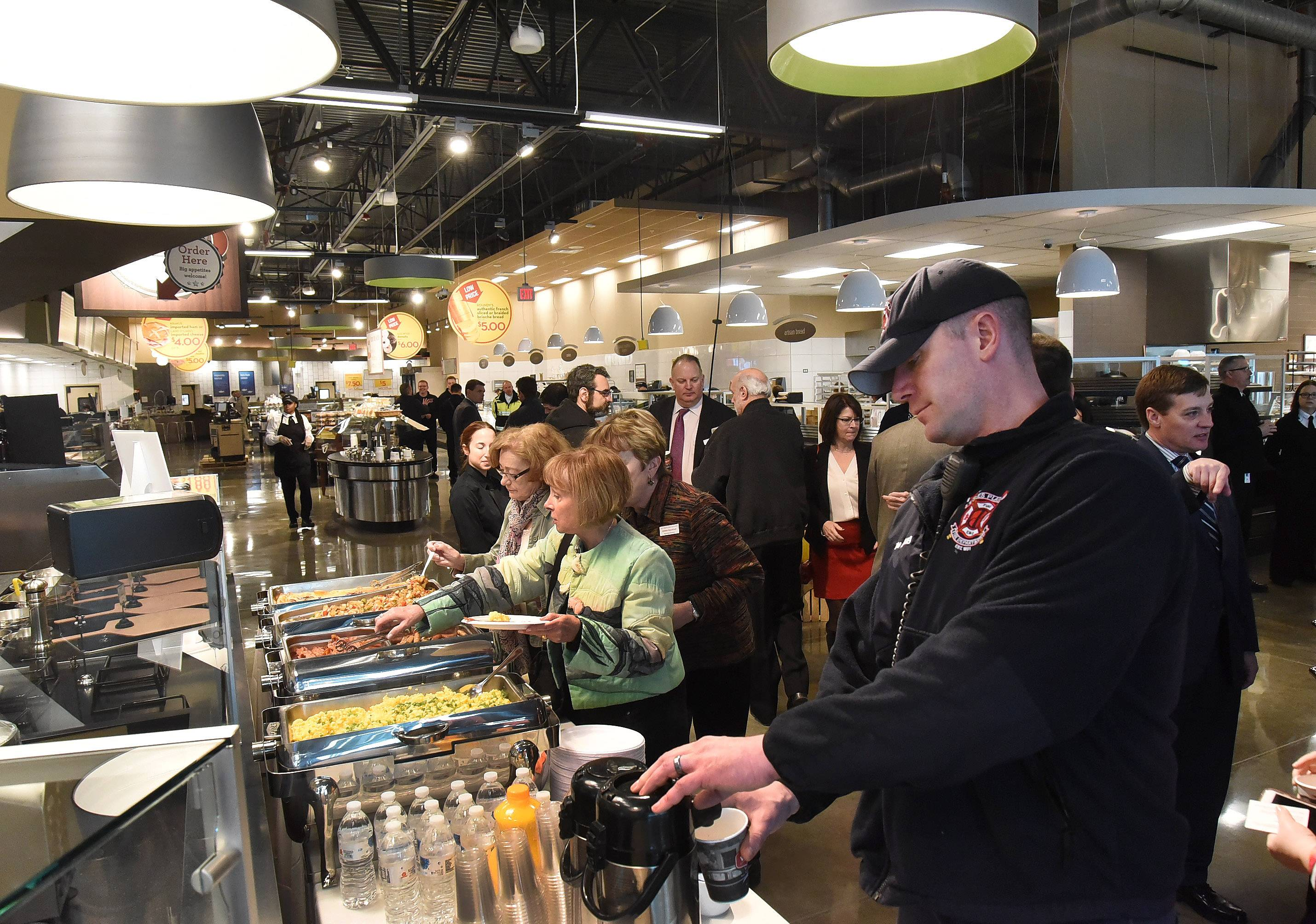 Guests help themselves to breakfast Monday, as city leaders and Mariano's officials gathered to celebrate the opening of the grocery store chain's newest location in Des Plaines. The store opens to the public at 6 a.m. Tuesday.