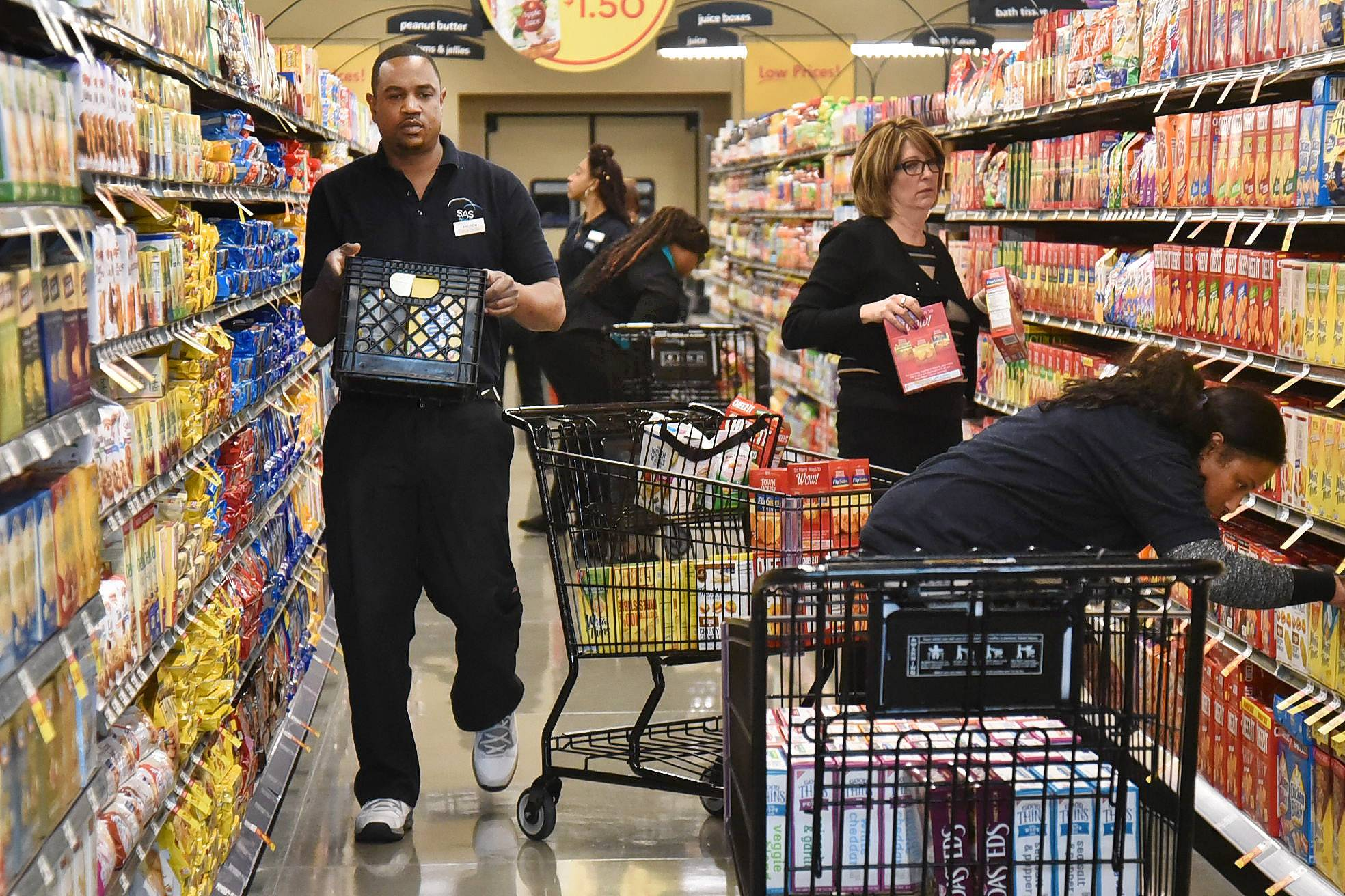 Andrew Young, left, of SAS food distributors, and fellow workers were busy stocking shelves for Tuesday's public opening of Mariano's newest location in Des Plaines.