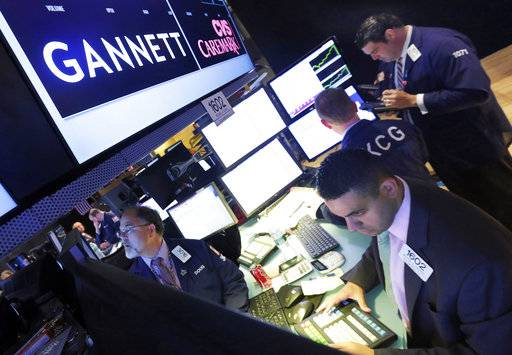 FILE - In this Aug. 5, 2014, file photo, specialist Michael Cacace, foreground right, works at the post that handles Gannett on the floor of the New York Stock Exchange. On Monday, March 20, 2017, Gannett named Joanne Lipman as the editor-in-chief of USA Today, one of the country's biggest newspapers.
