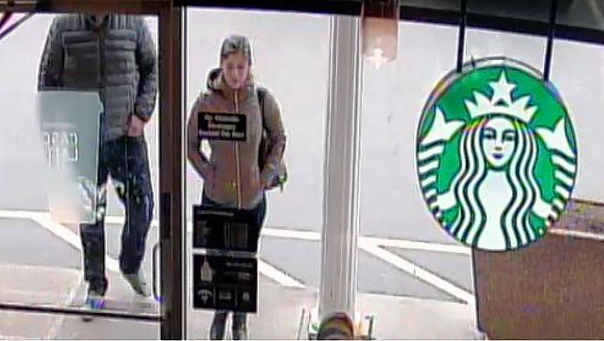 A surveillance image shows two people walking into a Starbucks after, police suspect, they stole a woman's wallet.