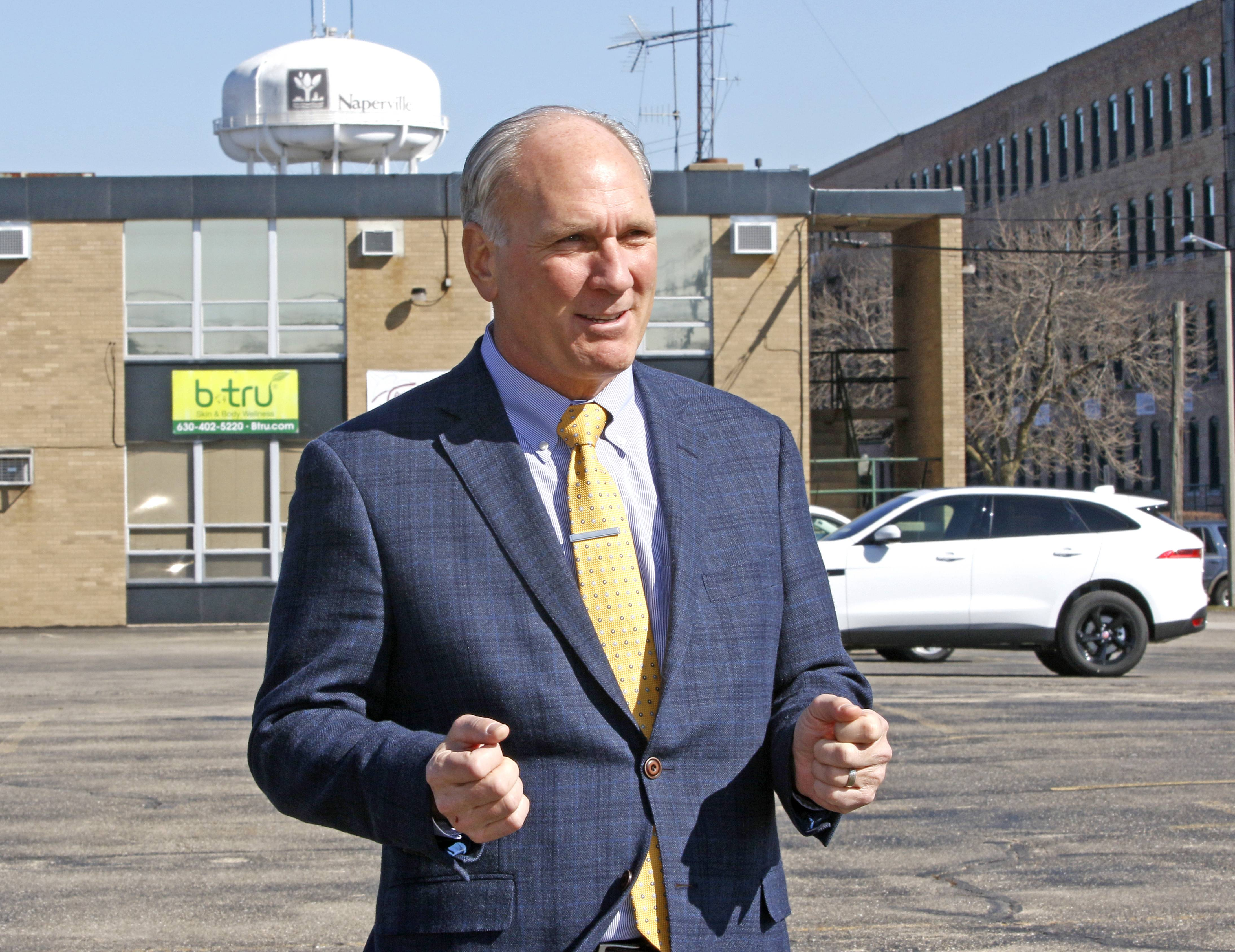 Naperville Mayor Steve Chirico says the city is seeking out-of-the-box ideas for eight acres of city-owned land around the 5th Avenue Metra station north of downtown, including the small business building and water tower site behind him.