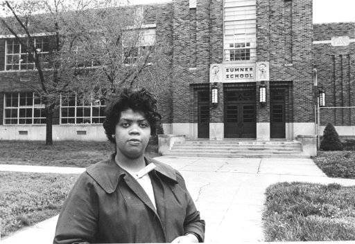 "FILE - This May 8, 1964 file photo shows Linda Brown Smith standing in front of the Sumner School in Topeka, Kan. The refusal of the public school to admit Brown in 1951, then nine years old, because she is black, led to the Brown v. Board of Education of Topeka, Kansas. In 1954, the U.S. Supreme Court overruled the ""separate but equal"" clause and mandated that schools nationwide must be desegregated. From the time Americans roll out of bed in the morning until they turn in, and even who they might be spending the night with, the court's rulings are woven into daily life in ways large and small."