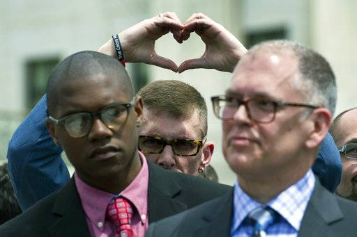FILE - In this April 28, 2015, file photo, plaintiff Rev. Maurice Blanchard, of Louisville, Ky., makes heart with his hands behind plaintiff plaintiff James Obergefell of Ohio, right, as they stand outside of the Supreme Court in Washington following a hearing on same-sex marriages. From the time Americans roll out of bed in the morning until they turn in, and even who they might be spending the night with, the court's rulings are woven into daily life in ways large and small.