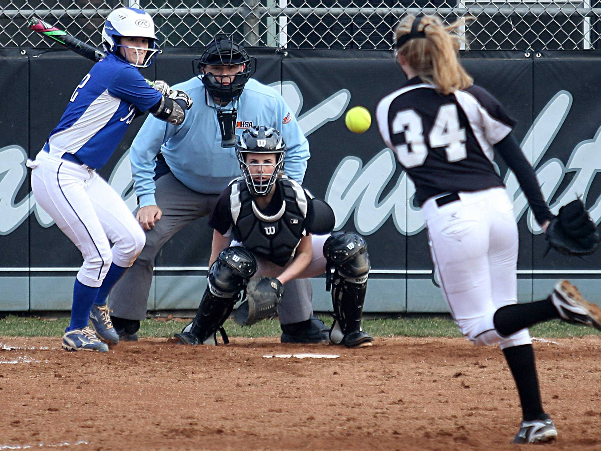 Kaneland's pitcher Emilee Erickson makes an offering as catcher Hailey Roach and  Burlington Central hitter Megan Wiater prepare during varsity softball at Kaneland Monday night.