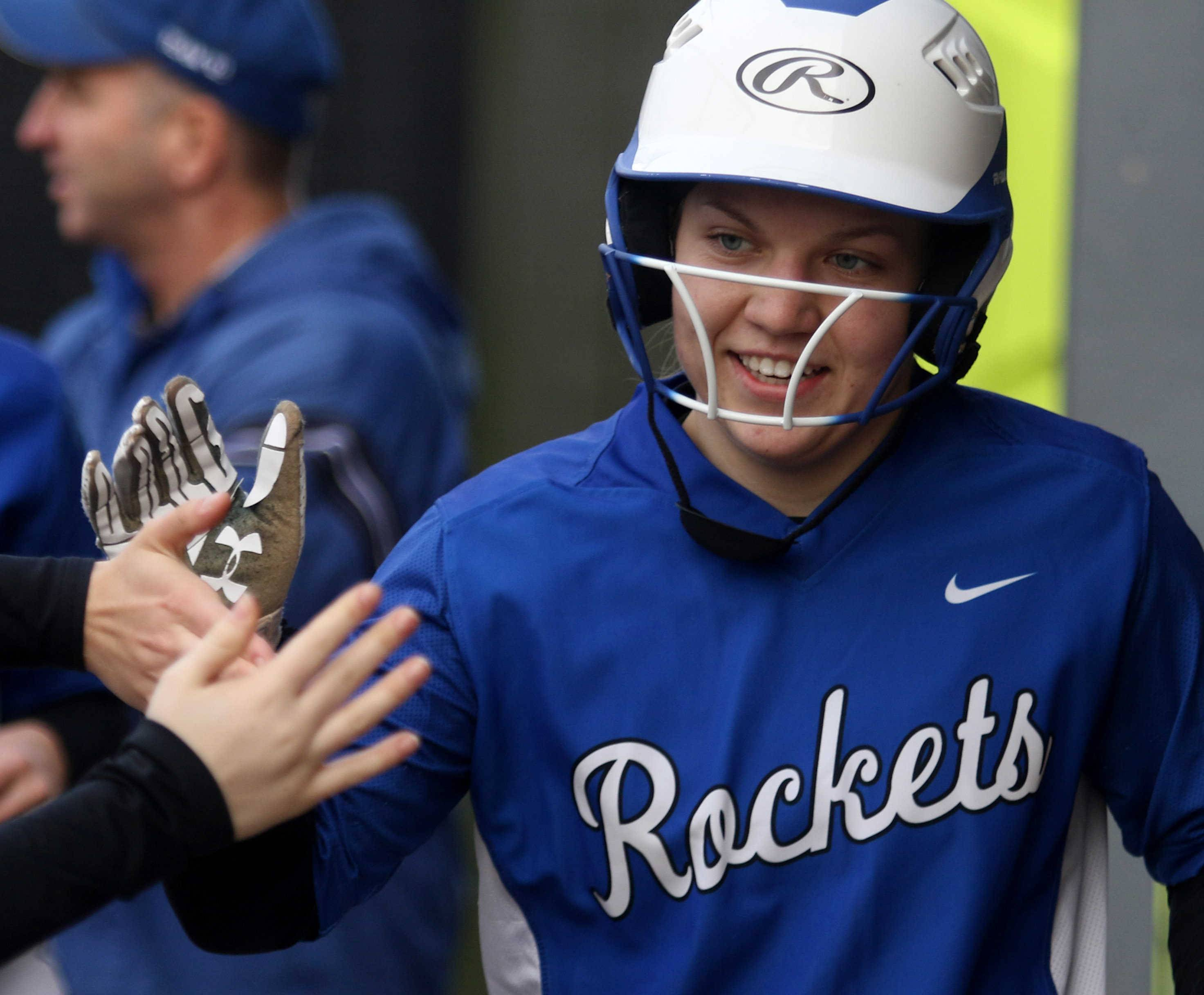Burlington Central's Danielle Yurgil is all smiles as she receives high fives after scoring during varsity softball action at Kaneland Monday night.